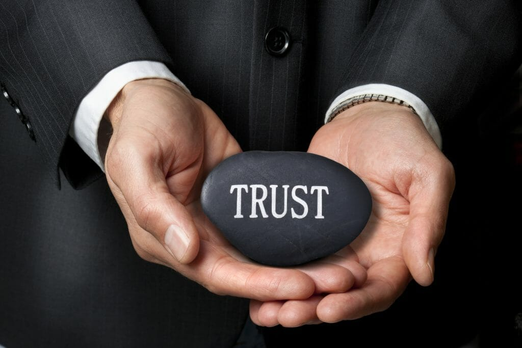 A man in a suit holds a rock that has trust written on it